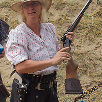 Competitor takes her weapon to inspection during the Cowboy Action Shooting European Championship in Dabas, Hungary on August 11, 2012. ATTILA VOLGYI