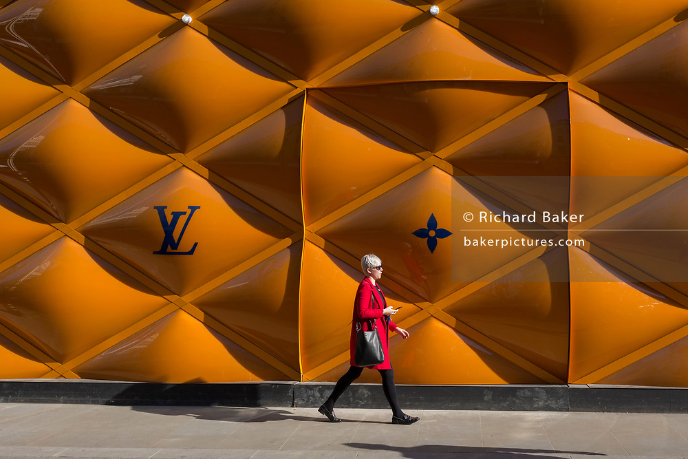 A lady shopper in a red coat walks past the temporary renovation hoarding of luxury brand Louis Vuitton in New Bond Street, on 27th February 2019, in London, England.