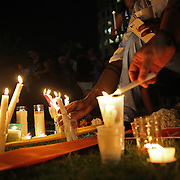 People place flowers and candles at a makeshift memorial during a vigil at the Dr. Phillips Center for the Performing Arts for the victims of a mass shooting at the Pulse nightclub Monday, June 13, 2016, in Orlando, Florida.  A gunman killed dozens of people in a massacre at the crowded gay nightclub in Orlando on Sunday, making it the deadliest mass shooting in modern U.S. history. (Alex Menendez via AP)
