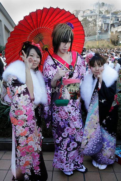 boy dressed in kimono posing for a picture with two girls Coming of Age festival, Seijin no hi, Japan
