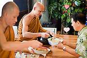 24 OCTOBER 2010 - CHANDLER, AZ:  SOMKIET, (green shirt) presents food to Ajahn MAHA AMPORN during the Ok Phansa services to mark the end of Buddhist Lent at Wat Pa, in Chandler, AZ, Sunday October 24. Buddhist Lent is a time devoted to study and meditation. Buddhist monks remain within the temple grounds and do not venture out for a period of three months starting from the first day of the waning moon of the eighth lunar month (in July) to the fifteenth day of the waxing moon of the eleventh lunar month (in October). Ok Phansa Day marks the end of the Buddhist lent and falls on the full moon of the eleventh lunar month, this year Oct 23. Wat Pa, a Thai Theravada Buddhist temple, celebrated Ok Phansa Day on October 24.    Photo by Jack Kurtz