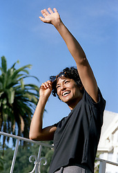 woman enjoying seeing someone she knows with a big smile and wave of the hand