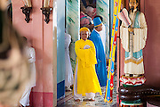 "29 MARCH 2012 - TAY NINH, VIETNAM:   Cao Dai clergy, in brightly colored robes, lead adherents into the prayer hall during the noon services at the Cao Dai Holy See in Tay Ninh, Vietnam. Cao Dai (also Caodaiism) is a syncretistic, monotheistic religion, officially established in the city of Tây Ninh, southern Vietnam in 1926. Cao means ""high"" and ""Dai"" means ""dais"" (as in a platform or altar raised above the surrounding level to give prominence to the person on it). Estimates of Cao Dai adherents in Vietnam vary, but most sources give two to three million, but there may be up to six million. An additional 30,000 Vietnamese exiles, in the United States, Europe, and Australia are Cao Dai followers. During the Vietnam's wars from 1945-1975, members of Cao Dai were active in political and military struggles, both against French colonial forces and Prime Minister Ngo Dinh Diem of South Vietnam. Their opposition to the communist forces until 1975 was a factor in their repression after the fall of Saigon in 1975, when the incoming communist government proscribed the practice of Cao Dai. In 1997, the Cao Dai was granted legal recognition. Cao Dai's pantheon of saints includes such diverse figures as the Buddha, Confucius, Jesus Christ, Muhammad, Pericles, Julius Caesar, Joan of Arc, Victor Hugo, and the Chinese revolutionary leader Sun Yat-sen. These are honored at Cao Dai temples, along with ancestors.   PHOTO BY JACK KURTZ"