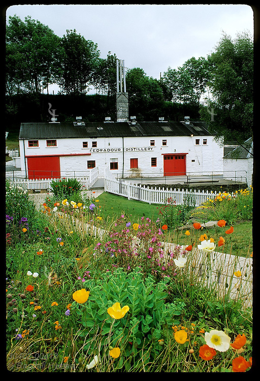 Wildflowers accent the red & white bldgs of Edradour Distillery, Scotland's smallest; Pitlochry Scotland
