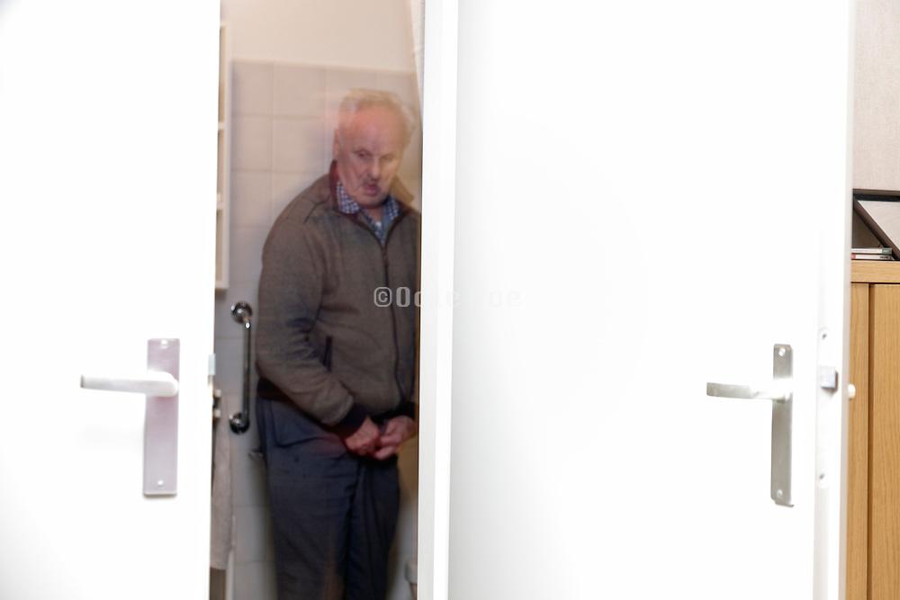 senior man standing in toilet room