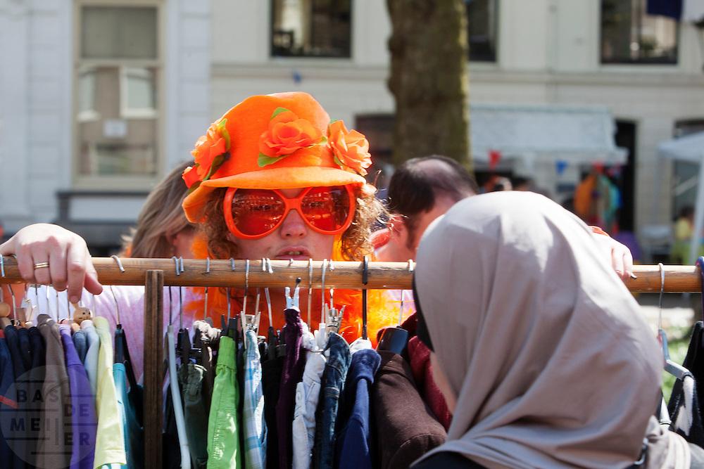 Een geheel in oranje gestoken vrouw probeert kleren aan een moslima te verkopen op de vrijmarkt in Utrecht tijdens Koninginnedag 2012.<br /> <br /> People are selling stuff at the flee market on Queensday in Utrecht.