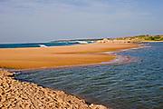 Landscape in Bundala National Park showing Indian Ocean waves breaking on a sand bar at the moth of the swamp area, Sri Lanka
