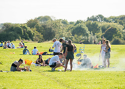"© Licensed to London News Pictures; 14/09/2020; Bristol, UK. Groups of people, some more than six in number, enjoy the sunshine and hot weather on Bristol Downs. From today Monday 14 September it is illegal to meet up socially in groups of more than six people, known as the ""Rule of Six"", in order to try and contain the spread of the covid-19 coronavirus pandemic, and police have said they will enforce the law with fixed penalty notices which will increase for repeat offenders. There are some exceptions to the new law such as larger families that live together or if a support bubble is greater than six. People should still practice social distance if they do not live in the same house hold or support bubble. Bristol recently recorded the biggest daily increase in 10 weeks of new cases of coronavirus, and nationally, 3,539 new cases have been confirmed, the highest rise for four months. Photo credit: Simon Chapman/LNP."