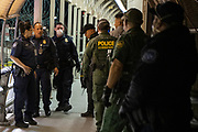 Customs and Border Protection agents walk past two Cuban men in the Migrant Protection Protocols program presenting at the Paso Del Norte International Bridge to change their asylum court dates amid the COVID-19 pandemic on April 1, 2020 between Ciudad Juárez, Chihuahua, Mexico and El Paso, Texas.