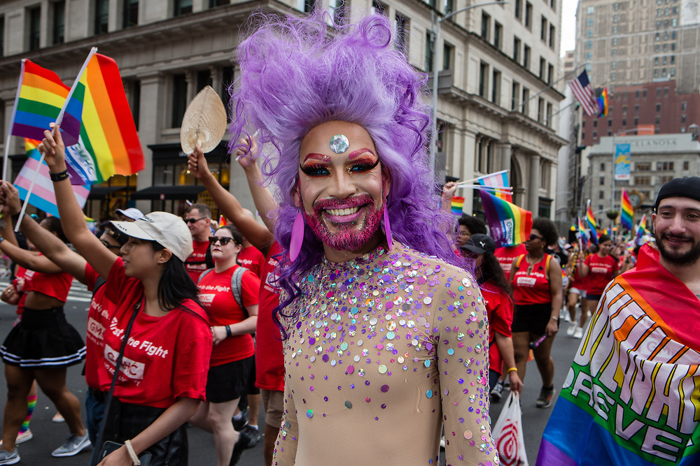 New York, NY - 30 June 2019. The New York City Heritage of Pride March filled Fifth Avenue for hours with participants from the LGBTQ community and it's supporters. A bearded man in a sparkly costume and purple hair smiles.