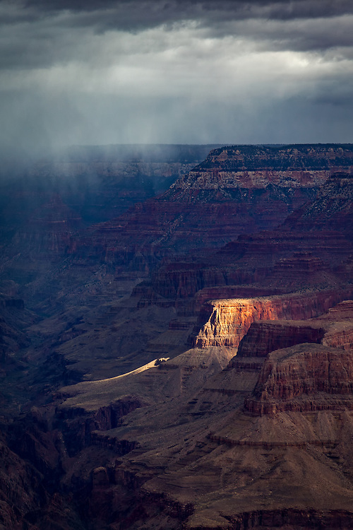 A single spot of light breaks through the rain and clouds on the South Rim of the Grand Canyon in Arizona.