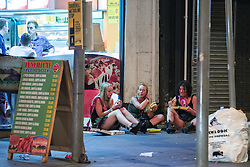 © Licensed to London News Pictures . 15/06/2014 . Manchester , UK . Three women sit on the pavement and eat takeaway food . People on a night out in Manchester City Centre overnight , following England's defeat to Italy in the World Cup . Photo credit : Joel Goodman/LNP