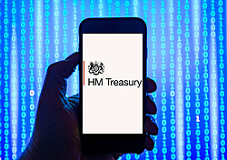 Person holding smart phone with   HM Treasury  logo displayed on the screen. EDITORIAL USE ONLY