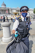 """A Police officer carries the possesions of photojournalist Craig Bernard in Trafalgar Square, central London on Sunday, Aug 9, 2020 - after they asked him to be sitting in their van and was going to be questioned in Holborn Police station. Bernard was covering a demonstrative action of the environmental activists' group Extinction Rebellion. A Police officer told a member of """"Legal Observers"""" in the scene that among the reason why he was arrested for allegedly committing a quote: """"Affray"""" and riding an uninsured e-scooter. (VXP Photo/ Vudi Xhymshiti)"""