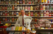 A portrait of a smiling 1990s shop keeper in his sweet store surrounded by jars of confectionery and his traditional pre-digital weighing scales, on 12th June 1992, in Frinton, Essex, England.