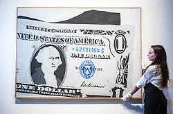 """© Licensed to London News Pictures. 08/06/2015. London, UK. A Sotheby's technician shows """"Silver Certificate"""" by Andy Warhol (est. £13m - £18m), at the preview of """"To the Bearer on Demand"""", a private collection of 21 works inspired by the US dollar, including Andy Warhol masterpieces, which will be auctioned on 1 and 2 July.  The collection is estimated to realise £50 million.  The painting on show is the artist's very first painting in his series of dollar paintings, and the only one painted entirely by hand. Photo credit : Stephen Chung/LNP"""