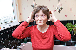 Woman; who has been undergoing Chemotherapy for breast cancer; putting on a wig to cover up hair loss as a result of the treatment,