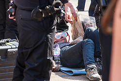 London, UK. 20th April 2019. Police officers use cutting equipment to remove climate change campaigners from Extinction Rebellion who had locked themselves using arm tubes at Oxford Circus following a policing operation to clear it of protesters earlier in the day. The heart of London's shopping district was blocked again for around two hours by the lock-ons on the sixth day of International Rebellion activities to call on the British government to take urgent action to combat climate change.