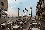 The Piazzetta with cafe tables and flying pigeons, Piazza San Marco, Venice, Italy
