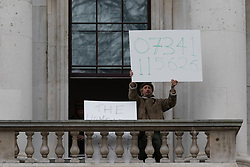 © Licensed to London News Pictures. 30/12/2015. London, UK. A protester holds a placard displaying a phone number on a balcony of the Royal Mint building. Squatters have occupied the former Royal Mint building, located opposite the Tower of London on the border of the City of London to protest against homelessness and highlight how empty buildings could provide shelter for rough sleepers. The site was previously used to manufacture British coins but is currently vacant and activists argue that this along with other vacant commercial buildings could be used to provide short term shelter for the homeless. Photo credit : Vickie Flores/LNP