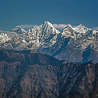 Mount Everest (background) and adjacent peaks tower behind lower foothills in the Khumbu region of Nepal's Himalaya.