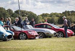 © Licensed to London News Pictures. 19/08/2017. Biggin Hill, UK. Visitors admire a line up of sports cars in the sunshine at the Biggin Hill Festival of Flight 2017. The two day festival takes place in the centenary year of the historic airport. The Red Arrows will be flying along with a Belgian F-16, the Czech Air Force,  a Spitfire and a Typoon. Photo credit: Peter Macdiarmid/LNP