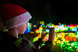 USA, Washington, Bellevue. Boy photographing at Garden d'Lights at Bellevue Botanical Garden during the holiday season.  MR