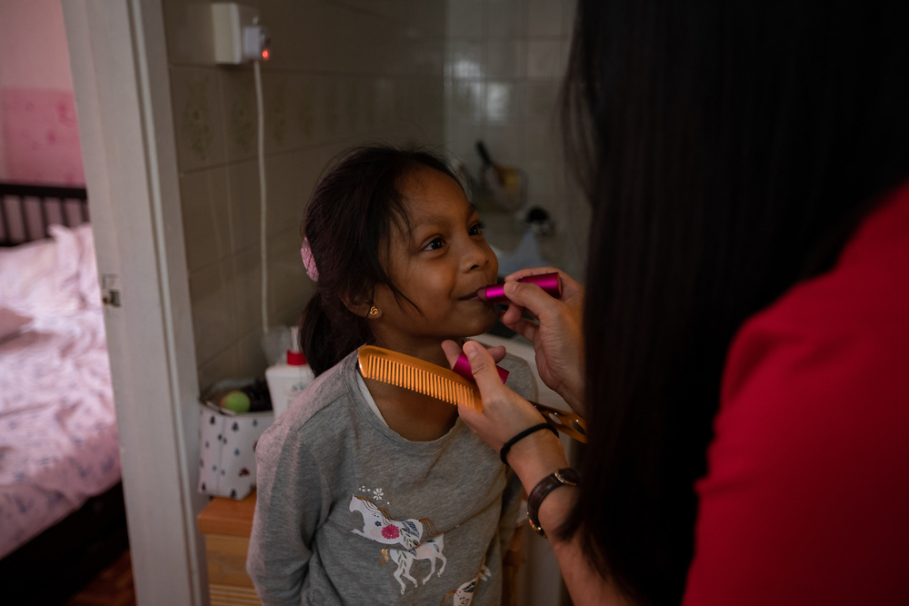 Vanessa Mae Rodel, 42, applies lipstick to her seven-year-old daughter Keana Nihinsa, at their home in Hong Kong, on March 21, 2019. / Photo: Maria de la Guardia