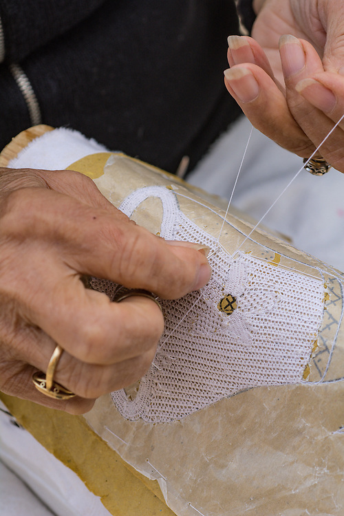 Old woman making lace by hand