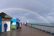 A man wearing blue shelters from a rain shower as a rainbow showing the spectrum of colours is seen arcing across the sky above Llandudno pier, on 4th October 2021, in Llandudno, Gwynedd, Wales.