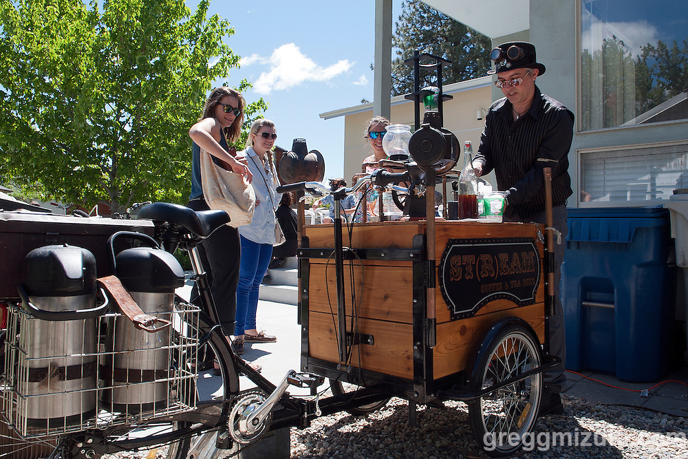Jodi Eichelberger prepares a complimentary drink as a perk of his ST(r)EAM Bike/Art tour through the Surel Mitchell Live-Work-Create District in Garden City, Idaho on April 30, 2016.<br /> <br /> Artists and venues on the tour included Surel's Place, Megan Levad, Sara Hill, Will Bennett, Victor Myers and Corridor Surf Shop, Geoffery Krueger, Karen Woods, Gina Phillips, Hindi Morland, Heidi Haislmaier and the new Telaya Winery where Segreto Wood Fired Pizza set up shop for the bike tour group.