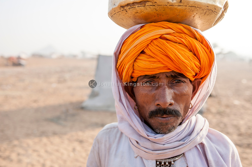 Portrait of a desert nomad carrying water on his head in a brass bowl.