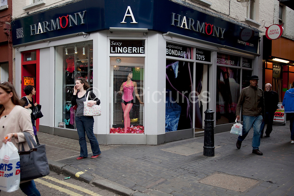 """Harmony sex shop in Soho, central London. In this seedy alley, there are sex shops, DVD shops, live sex shows and all manner of pornographic offerings. Soho continues to be the centre of the sex industry in London, and features numerous licenced sex shops. There is a clip joint on Tisbury Court and an adult cinema nearby. Prostitutes are widely available, operating in studio flats. These are sign-posted by fluorescent """"model"""" signs at street level."""