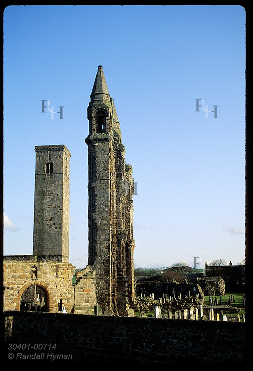 Late afternoon sun bathes ruins of church towers and cemetery on an April day in St. Andrews. Scotland