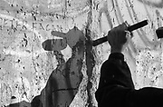 A West Berliner hammers a chisel to make a hole in the Berlin Wall. A trophy of divided oppressed times.