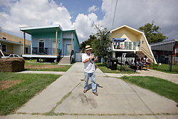 29 August 2015. Lower 9th Ward, New Orleans, Louisiana.<br /> Hurricane Katrina 10th Anniversary.<br /> Jo Crachiola waits for a second line to pass along Tennessee Street in front of Brad Pitt inspired make it Right homes as residents and mourners celebrate the lives of those lost to the storm. <br /> Photo credit©; Charlie Varley/varleypix.com.