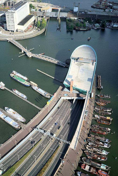 Nederland, Amsterdam, Oosterdok, 25-09-2002; Wetenschapsmuseum NEMO (voorheen New Metropolis) boven de ingang van de IJtunnel, in het water van het Oosterdok historische binnenvaartschepen; linksboven Hoofdpostkantoor (TPG, PTT); cultuurpolitiek, scheepvaart, verkeer;<br /> luchtfoto (toeslag), aerial photo (additional fee)<br /> foto /photo Siebe Swart