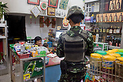 """Sept. 25, 2009 -- PATTANI, THAILAND: A Thai soldier on patrol for Muslim insurgents buys a newspaper in a Chinese owned small shop in Pattani, Thailand. Thailand's three southern most provinces; Yala, Pattani and Narathiwat are often called """"restive"""" and a decades long Muslim insurgency has gained traction recently. Nearly 4,000 people have been killed since 2004. The three southern provinces are under emergency control and there are more than 60,000 Thai military, police and paramilitary militia forces trying to keep the peace battling insurgents who favor car bombs and assassination.   Photo by Jack Kurtz / ZUMA Press"""