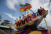 People enjoying the various rides at Adventure Island Funfair at Southend-on-sea, Essex. The town could be described as run down as while there are some signs of affluence, these are few and far between. The predominant atmosphere is quite rough feeling and quite poor. Southend is a seaside resort that is very popular with people from the East side of London due to it's close proximity, just an hour away by train along the Thames Gateway. With the decline of seaside resorts, from the 1960s much of the centre was developed for commerce and many of the original features were destroyed through redevelopment or neglect.