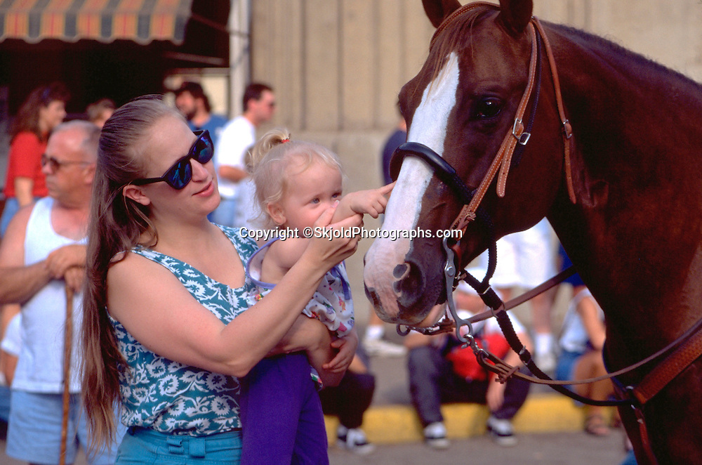 Mom and daughter touching head of horse age 30 and 1. Minnesota State Fair St Paul Minnesota USA