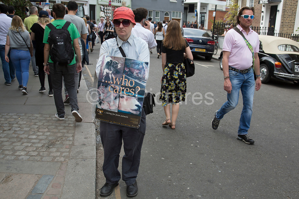 Man out promoting awareness for the charity Caring in World Farming Trust in London, United Kingdom.