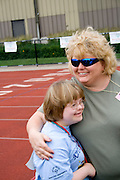 Mom hugging young daughter at award ceremony. Special Olympics U of M Bierman Athletic Complex. Minneapolis Minnesota USA