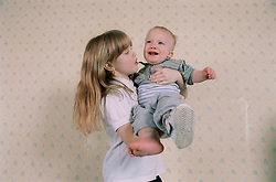 Young girl holding baby brother,