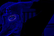 A one-eyed man uses his fingers to frame up a shot.  Blacklight photography.