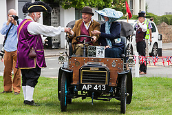 Datchet, UK. 30 June, 2019. Chris Brown, Official Town Crier of the Royal Borough of Windsor and Maidenhead, welcomes the occupants of 1904 Humberette as it completes the 48-mile Ellis Journey from Micheldever station near Winchester to Datchet. The Ellis Journey is a reenactment of the first recorded journey by a motorised carriage in England undertaken by pioneer automobilist Hon. Evelyn Ellis in his new, custom-built Panhard-Levassor on 5th July 1895. The original journey took place in contravention of the law because the Panhard exceeded a speed of 4mph and was not preceded by an attendant walking with a red flag.