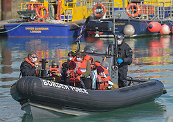 © Licensed to London News Pictures. 18/09/2021. Dover, UK.  Border force officials carry migrants ashore as they arrive at Dover Harbour in Kent. Migrants are continuing to attempt the crossing from France as the weather improves this week. Photo credit: Stuart Brock/LNP