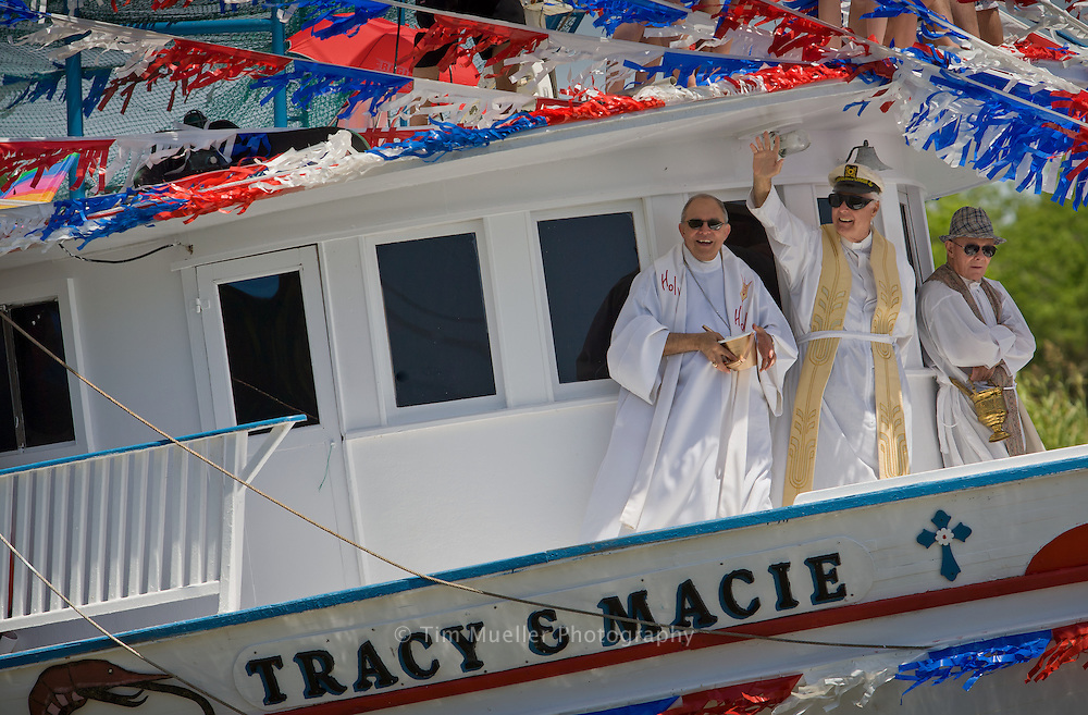 Father Frederic Brunet, center, of St. Joesph's Catholic Church in Chauvin, La. waves during the 2008 Blessing of the Boats. This Cajun community has continued the ritual since its adoption in the late 1920s when shrimpers lined up to have their boats blessed at St. Joseph's Catholic Church.
