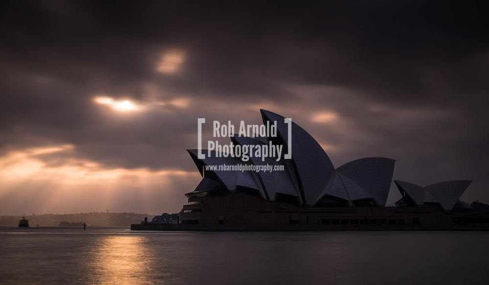 Sun rays pierce the early morning cloud cover over Sydney Opera House.