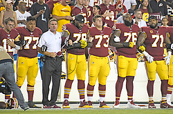 """From left to right: Washington Redskins quarterback Colt McCoy (12), offensive guard Shawn Lauvao (77), head coach Jay Gruden, offensive tackle Ty Nsekhe (79), center Chase Roullier (73), offensive tackle Morgan Moses (76), and offensive tackle Trent Williams (71) lock arms in solidarity as the national anthem is sung prior to the game against the Oakland Raiders at FedEx Field in Landover, Maryland on Sunday, September 24, 2017. The Redskins chose to demonstrate prior to their nationally televised contest following tweets earlier in the day from United States President Donald J. Trump urging owners to """"fire or suspend"""" players who participated in the protests by not standing for the anthem. Photo by Ron Sachs/CNP/ABACAPRESS.COM"""
