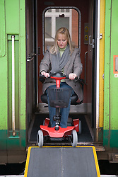 Woman steering electric mobility scooter down access ramp to board a train,